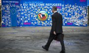 Demonstrators use a photo wall in Brussels to call for a generous EU refugee policy. (© picture-alliance/dpa)