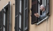 A man in Rome applauding doctors and nurses from his window. (© picture-alliance/dpa)