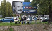 Members of the opposition Együtt party in front of a government billboard criticising Soros ist. (© picture-alliance/dpa)