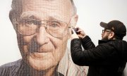 A visitor to the Ikea museum in Almhult in front of a portrait of Kamprad. (© picture-alliance/dpa)