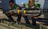 Sailors load a rocket on board the missile destroyer USS Bainbridge which is part of the USS Abraham Lincoln Carrier Strike Group. (© picture-alliance/dpa)