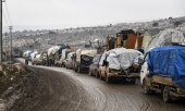 People fleeing towards the Syrian-Turkish border with heavily loaded vehicles. (© picture-alliance/dpa)