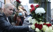 Activists with red and white flowers in front of the Belarusian embassy in Moscow. (© picture-alliance/dpa)