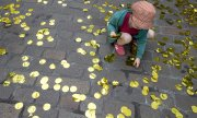 A child collects golden confetti at a get-together of advocates for a universal basic income. (© picture-alliance/dpa)