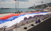 "Youths unfurl a Russian flag in Yalta on ""Russia Day"" in 2014. (© picture-alliance/dpa)"