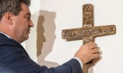 Bavaria's state premier Markus Söder hanging a cross on the wall of his office on 24 April 2018. (© picture-alliance/dpa)