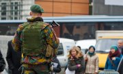 Belgian soldiers patrol in front of the seat of the European Council to protect the meeting of foreign ministers. (© picture-alliance/dpa)