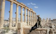A Syrian soldier takes down an IS flag in Palmyra. (© picture-alliance/dpa)