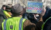 A demonstrator holds a sign bearing the words: Anti-Semitism, Islamophobia, Racism - not in our name. (© picture-alliance/dpa)
