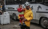 A member of the White Helmets bears a child in his arms in May 2018 after the arrival of a convoy carrying opposition fighters and their families from Damascus. (© picture-alliance/dpa)