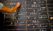 "A woman writing ""peace"" in various languages in Barcelona. (© picture-alliance/dpa)"