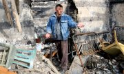 A man stands amid the ruins of his bombed-out house in Donetsk on 9 April 2021. (© picture-alliance/AP)