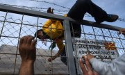 An Afghan refugee clambers over the fence at the border between Greece and Macedonia in Idomeni. (© picture-alliance/dpa)