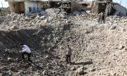Men standing among destroyed houses in Idlib on 22 August 2019. (© picture-alliance/dpa)